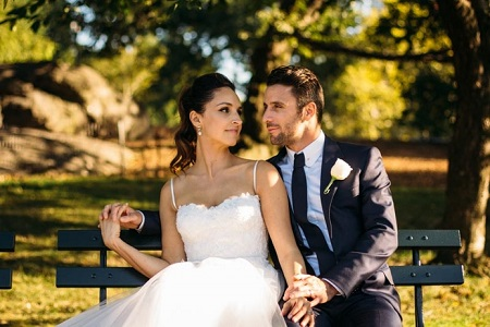 Central park wedding couple sitting on bench during golden hour