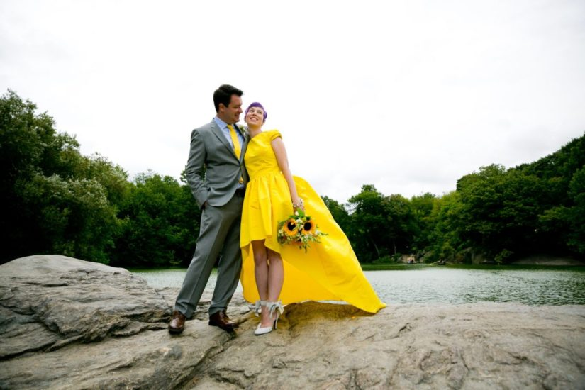 Groom and bride in yellow wedding dress standing next to The Lake