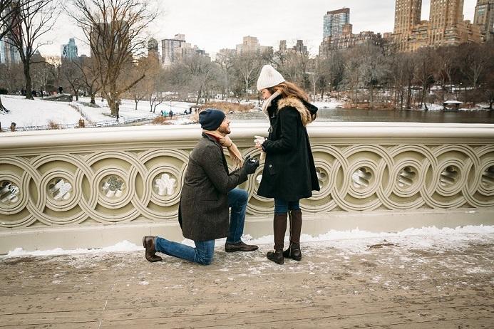 Man on one knee proposing to girlfriend on Bow Bridge in winter