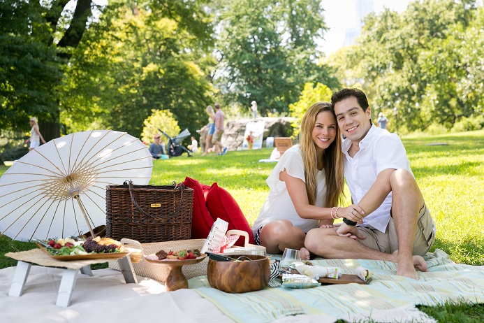 Newly engaged couple sitting next to romantic picnic setup