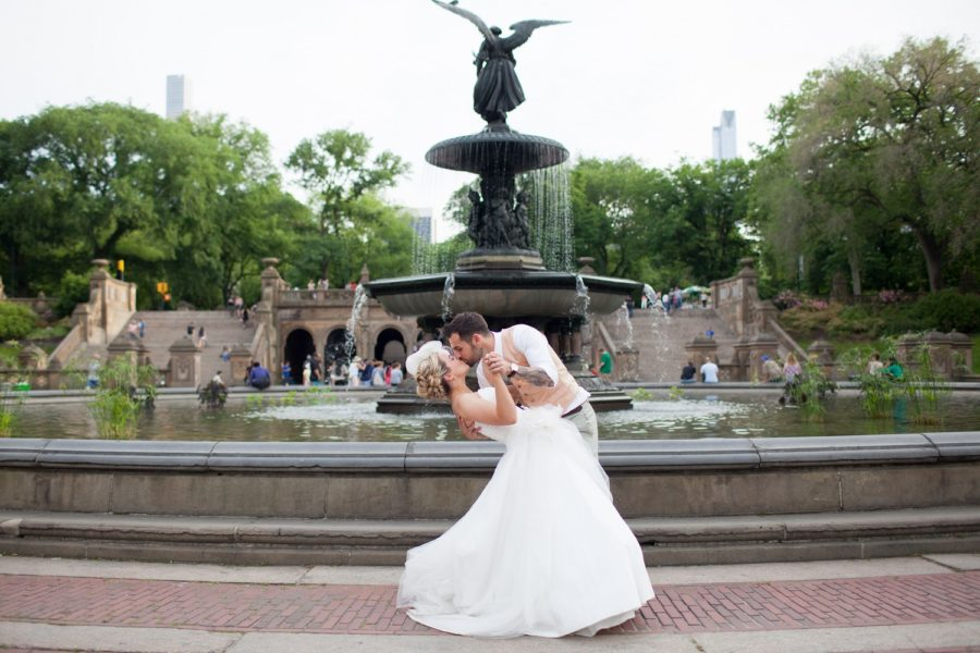 Groom dips bride and kisses her in front of Bethesda Fountain Central Park