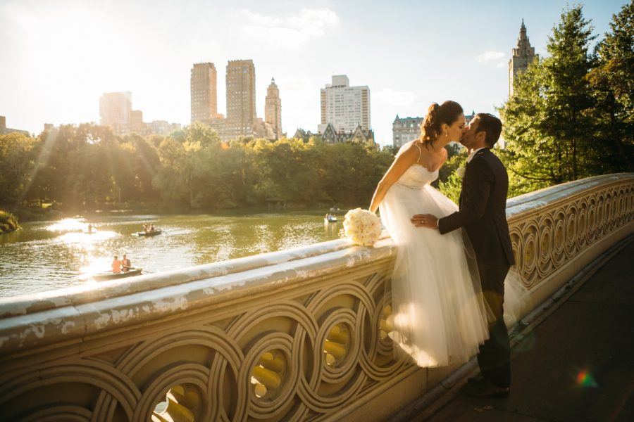 Newlyweds kiss on Bow Bridge during golden hour