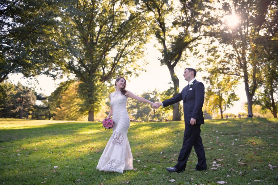 Newlyweds hold hands and walk along Cherry Hill Central Park